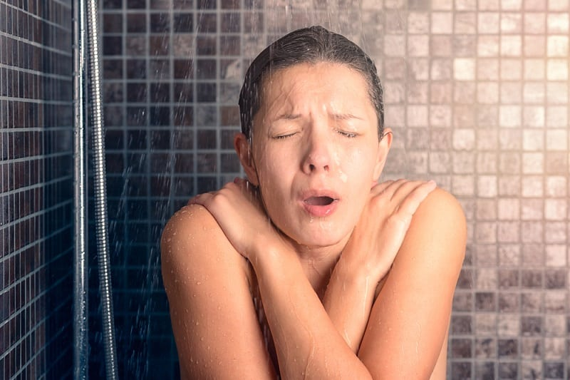 Young Woman Reacting While Taking Cold Shower